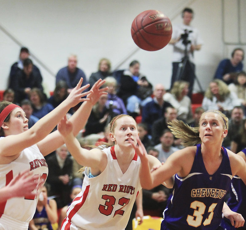 Emily Gray, left, and Hope Owen of South Portland reach for a loose ball along with Kylie Libby of Cheverus. Cheverus won, 43-33.