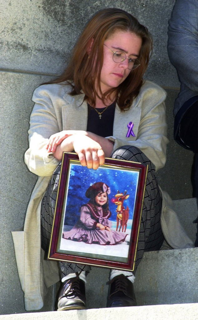 Christy Marr sits outside the State House in Augusta after an April 2003 news conference. The 2001 death of Marr's 5-year-old daughter Logan, who was in foster care at the time, led to major changes in Maine's system. One of those changes was an emphasis on placing children with family members.