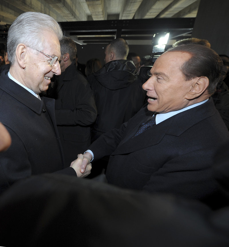 Italian Premier Mario Monti, left, and former Premier Silvio Berlusconi meet in Milan, Italy, on Sunday. Berlusconi spoke in defense of Benito Mussolini for allying himself with Hitler.