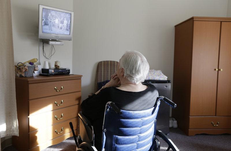 An elderly woman watches