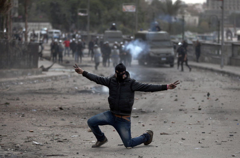 An Egyptian protester, part of the Black Bloc, flashes the victory sign during clashes with police in Cairo on Monday.