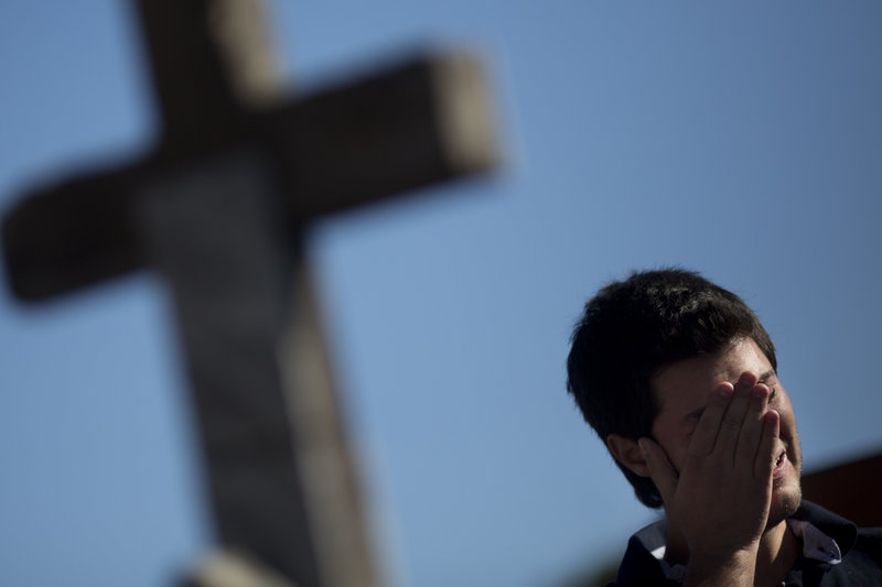 A man cries Monday at the burial of a victim who died in the nightclub fire in Santa Maria, Brazil.