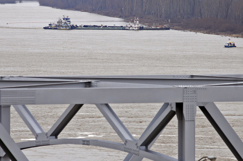 The towboat Nature's Way Endeavor, background, holds a barge against the western bank of the Mississippi River on Monday. The barge was leaking oil after hitting a bridge.