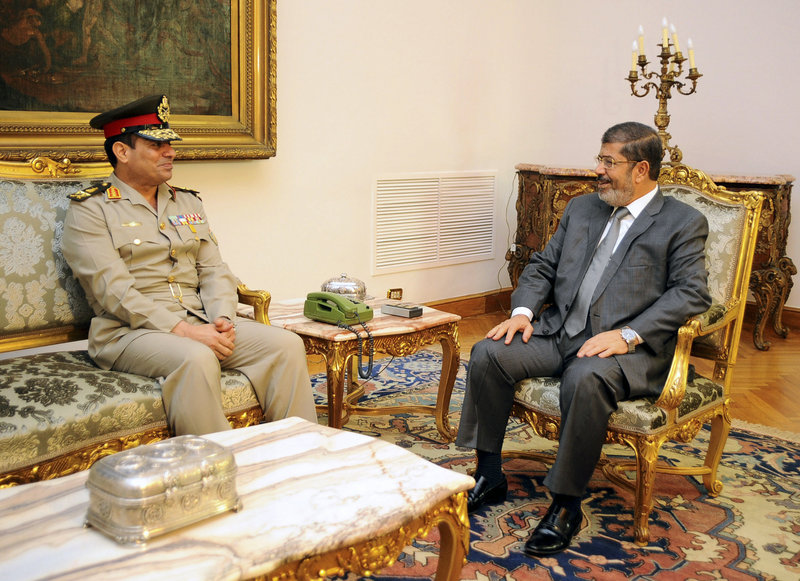 Gen. Abdel-Fattah el-Sissi, Egypt's defense minister, left, meets with President Mohammed Morsi in Cairo on Monday. On Tuesday, the army chief warned the state could collapse.