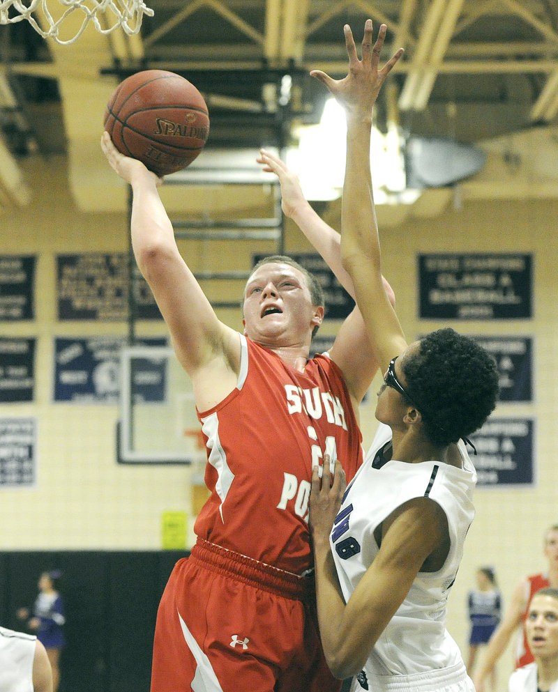 Conner MacVane of South Portland powers his way to the basket Tuesday night while guarded by Ahmed Ali of Deering.