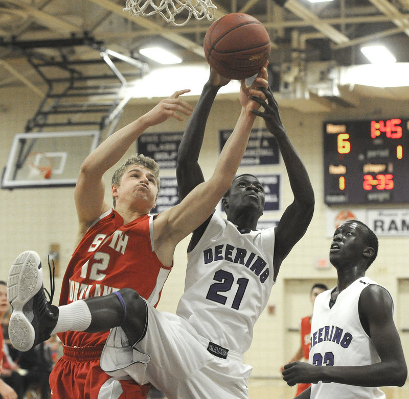 Ahmed Ismail Ahmed of Deering, center, attempts to keep a rebound from Ben Burkey of South Portland during the first quarter of their SMAA game Tuesday night. South Portland won, 53-38.
