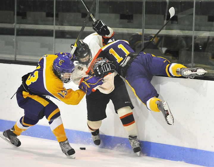 Andrew McGillivray, left, and Patrick Sullivan of Cheverus combine to knock Parker Wild of Brunswick off the puck behind his goal Wednesday during Cheverus' 4-1 victory in a schoolboy hockey game at Watson Arena in Brunswick.