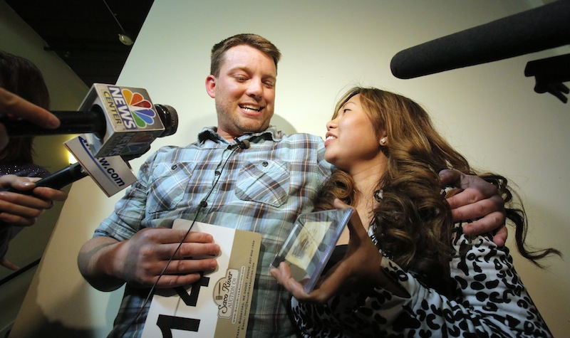 Jason Leblanc and his girlfriend Melinda Yung talk with the media after LeBlanc won the 1865 Brooklyn Atlantics card with and $80,000 bid at the Saco River Auction Company in Biddeford on Wednesday, Feb. 6, 2013. LeBlanc is from Newburyport, Mass.