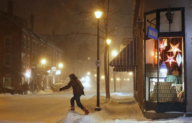 A pedestrian crosses Fore Street, Friday night, Feb. 8, 2013, as the snow continues to fall in Portland.