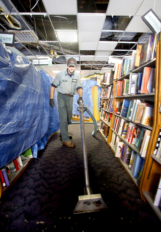 Dustin Souza sucks up the water in the carpet at Longfellow Books in Portland on Sunday. The second-floor sprinkler pipe froze and burst Saturday night during the blizzard, causing extensive water damage to the books and building.