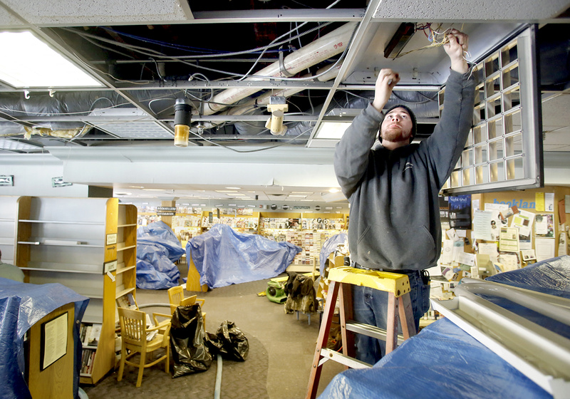 Tony Napolitano of T.A. Napolitano Inc. disconnects the lights Sunday at Longfellow Books in Portland, which were damaged from water after a second-floor sprinkler pipe froze and burst Saturday night during the blizzard.