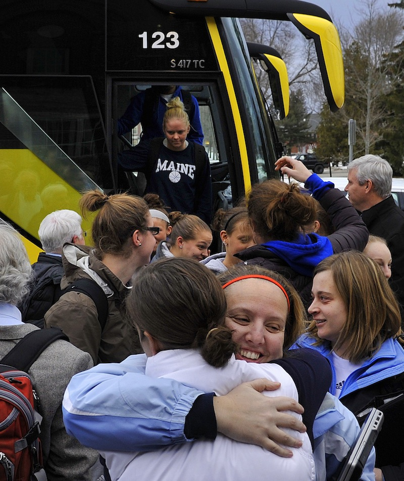 Assistant coach Amy Vachon receives a hug from former director of basketball operations Tracey Guerrette as the University of Maine women's basketball team returned to Orono on Wednesday evening, Feb. 27, 2013, after being involved in a harrowing crash on I-95 in Massachusetts on Tuesday night.