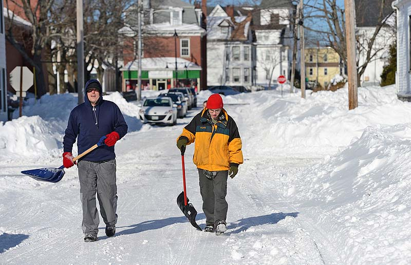 Chris Dyer, left, and Michael Demers of Saco make their way down School Street with shovels in hand as they look for driveways to shovel Sunday.