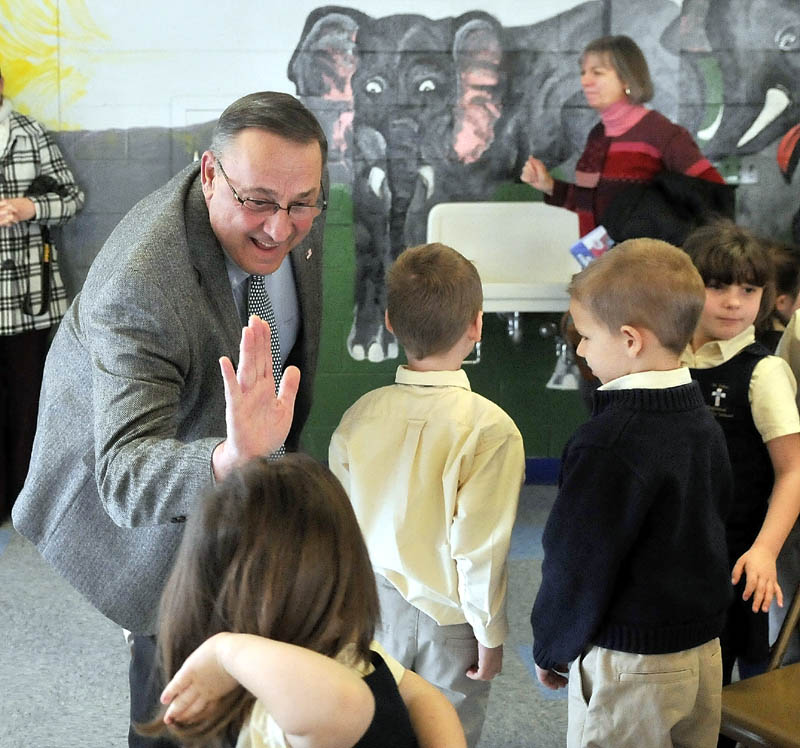 Gov. Paul LePage greets students after reading to the student body at St. John Regional Catholic School in Winslow on Friday.