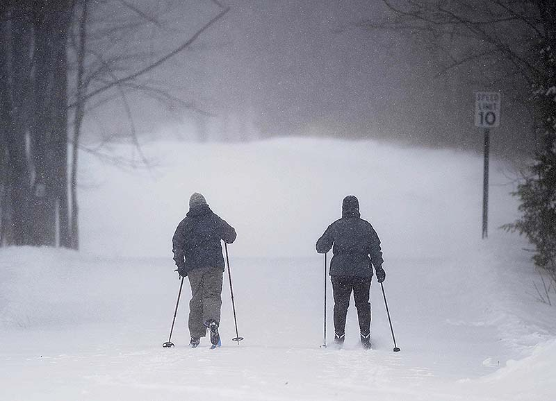 Skiers put fresh tracks on Quarry Road as snow falls in Waterville on Saturday, Feb. 9, 2013.