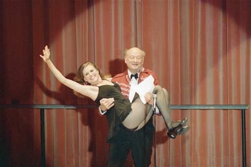 In this March 8, 1987, photo, New York Mayor Ed Koch gives a lift to Broadway dancer Ann Reinking during a performance of political satire on at the annual Inner Circle gathering of the New York Press Club in New York.