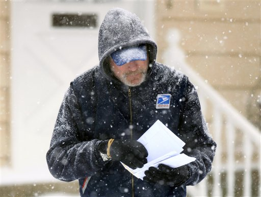 In this Saturday Dec. 19, 2009 file photo, U. S. Post Office letter carrier Tim Bell delivers the mail during a snow storm in Havertown, Pa. The financially struggling U.S. Postal Service says it will stop delivering mail on Saturdays but continue to deliver packages six days a week under a plan aimed at saving about $2 billion a year. In an announcement scheduled for later Wednesday Feb. 6, 2013, the service is expected to say the Saturday mail cutback would begin in August. (AP Photo/Jacqueline Larma)