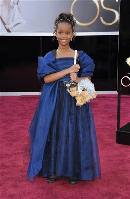 Quvenzhane Wallis wears an Armani Junior navy-blue dress with black, navy and silver jewels scattered on the skirt and a big bow on the back as she arrives for the Academy Awards.