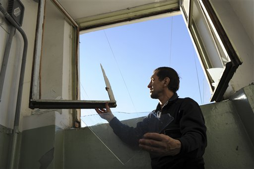 A local resident assesses damage to a window broken by a shock wave from a meteor explosion in Chelyabinsk, about 930 miles east of Moscow, on Friday.