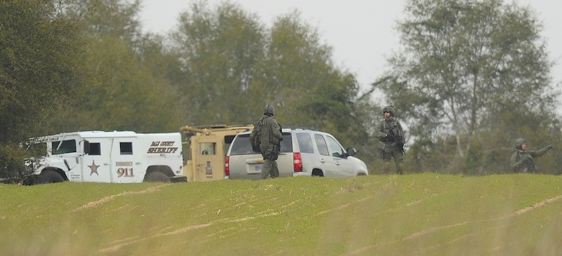 Armed law enforcement personnel station themselves near the property of Jimmy Lee Sykes, Monday, Feb. 4, 2013 in Midland City, Ala. Officials say they stormed a bunker in Alabama to rescue a 5-year-old child being held hostage there after Sykes, his abductor, was seen with a gun. (AP Photo/AL.com, Joe Songer) Midland city shooting