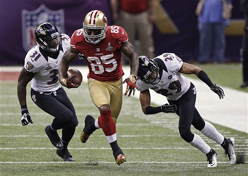San Francisco 49ers tight end Vernon Davis (85) runs with the ball as Baltimore Ravens safety Bernard Pollard (31) and cornerback Cary Williams (29) give chase during the first half of Super Bowl XLVII.