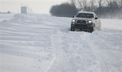 A truck makes its way along a snow covered road in Sedgwick County, Kan., on Tuesday. The storm dropped a half-foot or more of snow across Missouri and Kansas and cut power to thousands. Gusting winds blew drifts more than 2 feet high and created treacherous driving conditions for those who dared the morning commute.