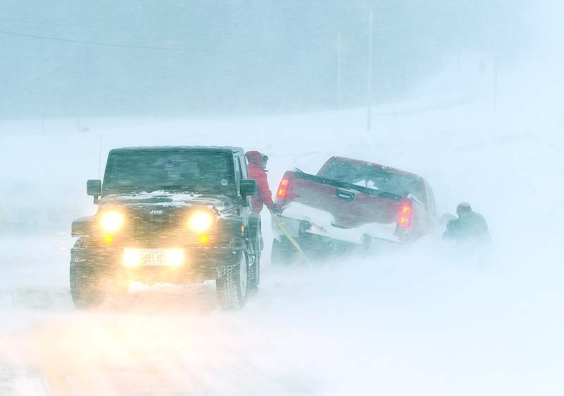 A motorist helps another getting back on the road as blizzard conditions make driving very dangerous along Route 114 in Gorham on Saturday.