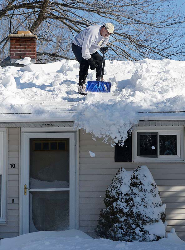 Kevin McPherson of Pleasant View Drive in Saco shovels off his roof on Sunday.
