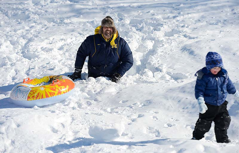 Brock Hieger of Saco sinks up to his waist in snow as he walks up a sliding hill at Saco Middle School on Sunday. Heiger was helping his 2-year-old son Gavin, right, when Gavin decided to walk on his own.