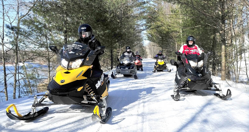 Scott Newton, left, of North Country Rivers in Bingham, leads a group of snowmobilers down the Interconnected Trail System 87 trail in February 2012. Snowmobilers will try to break the Guinness World Record for the largest snowmobile parade Saturday as part of a fundraiser for the Cystic Fibrosis Foundation of Northern New England.