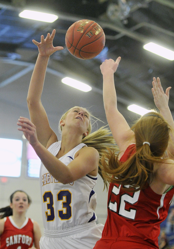 Heather LeBlanc, right, of Sanford knocks away a shot by Kylie Libby of Cheverus during their Western Class A quarterfinal Monday at the Portland Expo. Cheverus came away with a 31-26 victory.