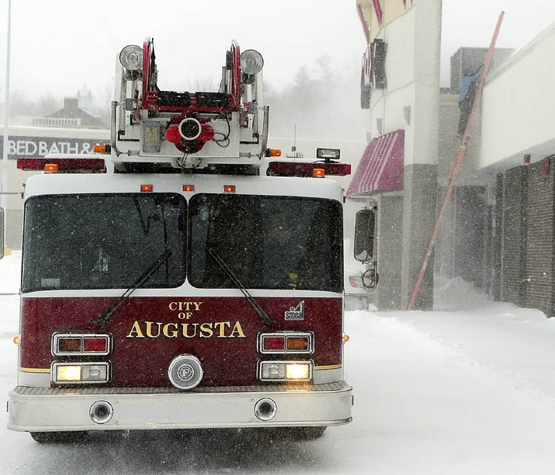An Augusta ladder truck sits in front of Turnpike Mall as an Augusta fuel technician climbs onto the roof to check the heating system around 3:20 p.m. on Saturday Feb,. 9, 2013 in Augusta. The fire department found high carbon-monoxide levels in the front of the building.