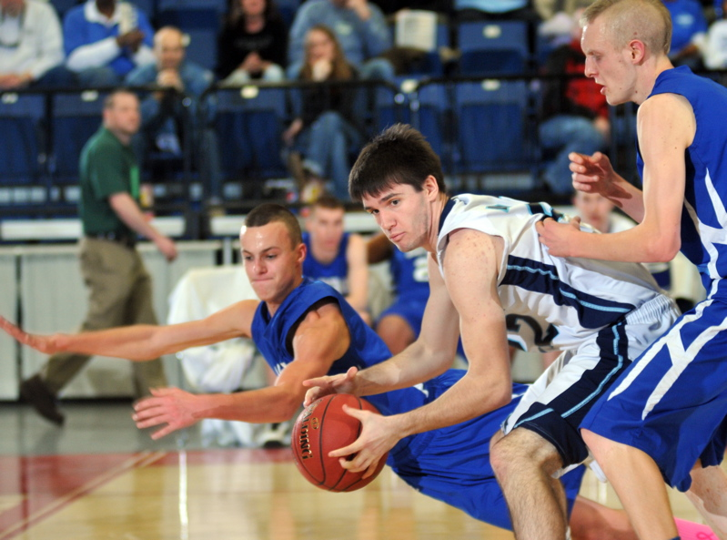 Kaine Hutchins of Dirigo picks up a loose ball between Anthony Langella-Laws, left, and James Strohm of Old Orchard Beach during their Western Class C quarterfinal Monday at the Augusta Civic Center. Third-seeded Dirigo rallied for a 50-47 win over the No. 6 Seagulls.