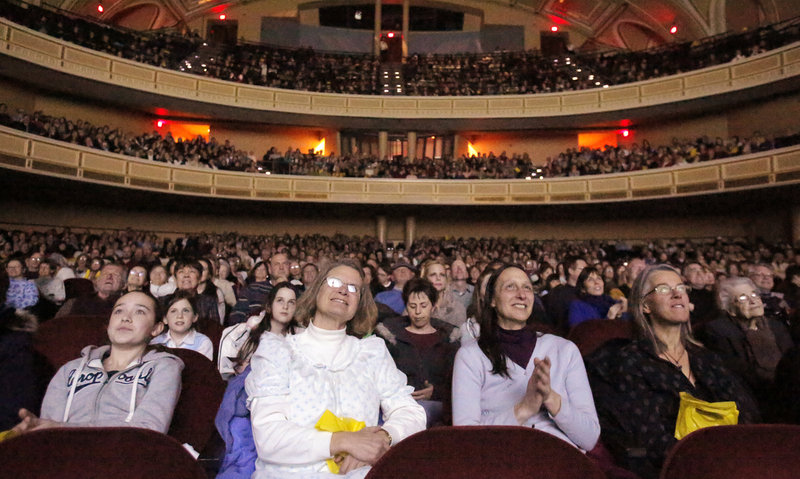 Sandi Radis, second from left and Robin Walden, both of Peaks Island, watch the opening scene of the film The Sound of Music during the Sing-A-Long-A Sound of Music at Merrill Auditorium on Friday, February 1, 2013.