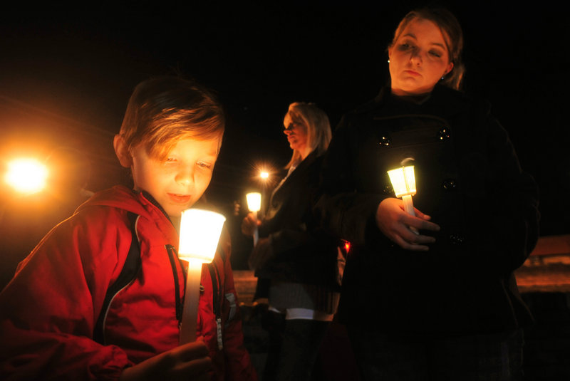 Cade Smith, 6, holds a candle as his mother, Brandi, looks on during a candlelight vigil Friday in Midland City, Ala.