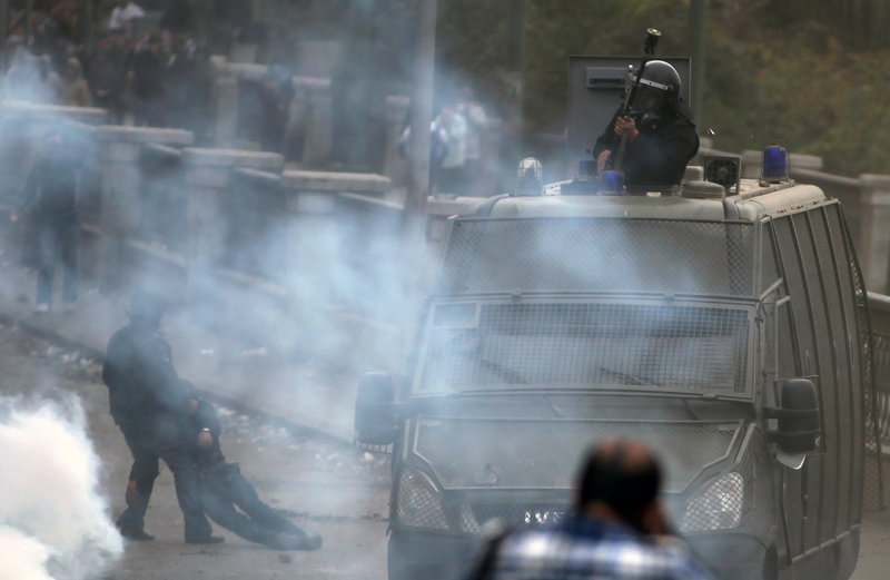 A protester removes an injured man, left, during clashes with riot police Jan. 28 near Tahrir Square in Cairo. A week of violent protests claimed more than 60 lives nationwide.