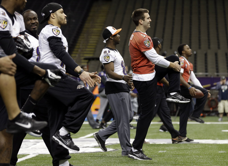 Joe Flacco, right, and his Baltimore Raven teammates warm up Saturday at the Superdome during a walkthrough for the Super Bowl against the San Francisco 49ers.