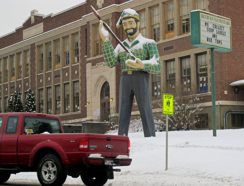 A statue of a logger stands outside a school in St. Maries, Idaho, near where a survivalist compound is planned.