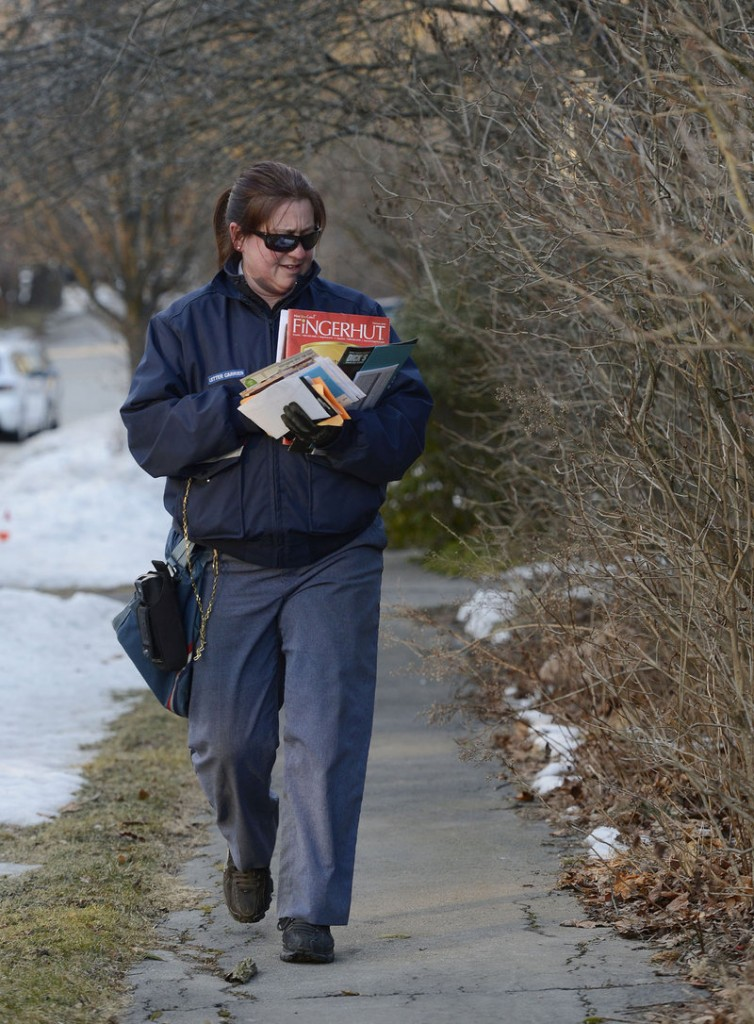 Mail carrier Carrie Estes sorts through mail on Bradley St. in Portland during her delivery route Wednesday, February 6, 2013. The U.S. Postal Service will stop delivering mail on Saturdays in an effort to save about $2 billion annually.
