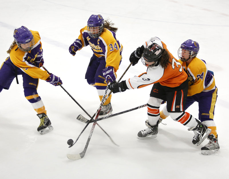 Cheverus defenders Kate Brewer, left, Katie Roy and Paige Severance, right, converge on Brea Rivard of Biddeford during the second period of Cheverus' 7-4 victory in a Western Maine quarterfinal Wednesday night.