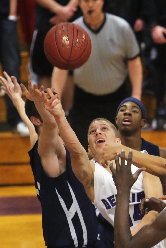 Dominic Lauture of Deering attempts to get to a rebound ahead of Nate Smart of Portland, left, during Deering's 37-30 victory at home Thursday night.