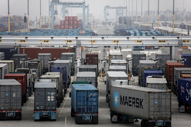 Trucks wait to be loaded at the Port of Los Angeles in December. A separate Commerce Department report Friday showed wholesale stockpiles declined in December, which could offset some of the gain from trade.