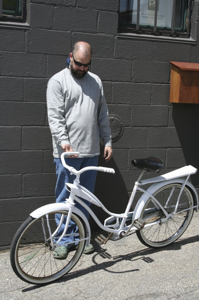 John Rooks shows one of eight bicycles used in an ad-hoc bike-sharing program he ran for two years in Portland.