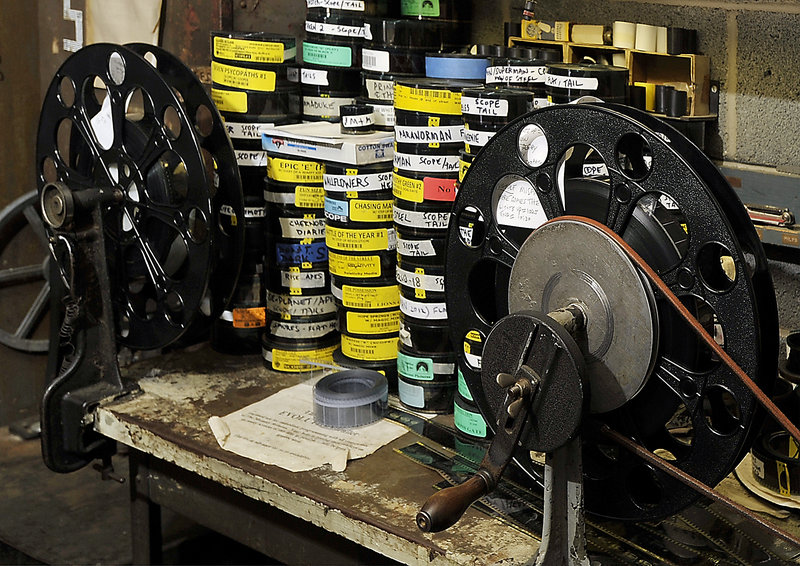 Here, dozens of short films and cartoons, that are usually shown before the main feature, sit on a work bench next to the theater's old-fashioned film reels.