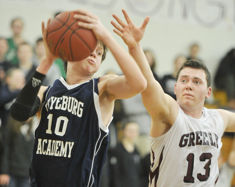 Fryeburg's Jonathan Burk pulls in a rebound against Greely's Bailey Train during Tuesday night's game in Cumberland, won by Greely.