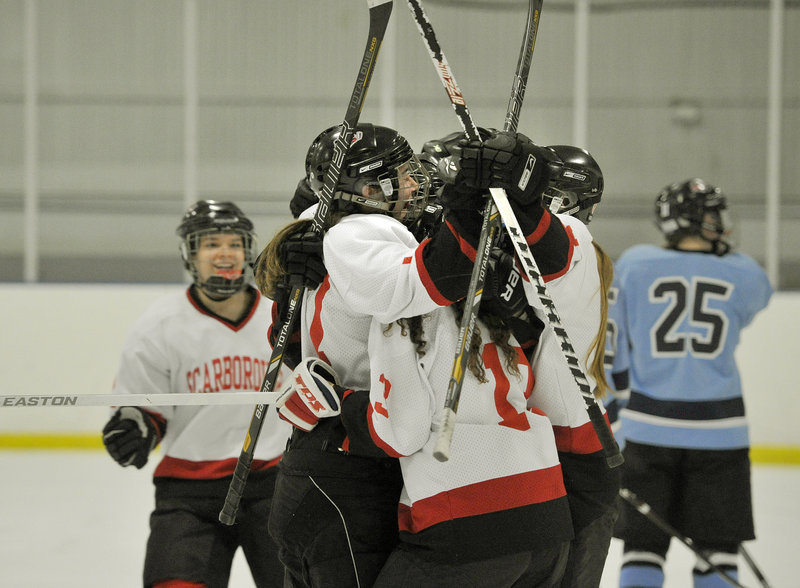 Sarah Martens is surrounded by teammates after scoring the second-period goal that stood up as the winner for Scarborough.