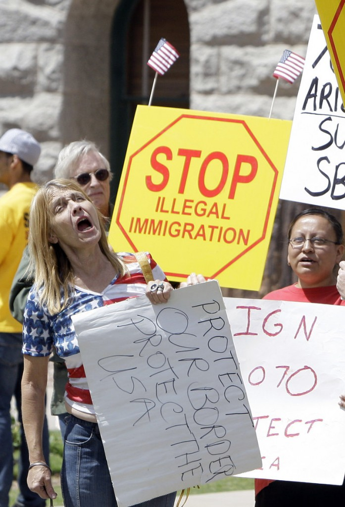 "Supporters rally in Phoenix just before Arizona Gov. Jan Brewer signed a tougher immigration bill into law on April 23, 2010. The Democratic Party and Big Business are conspiring in favor of lifting immigration limits ""to keep America flooded with low-wage labor,"" a reader says."