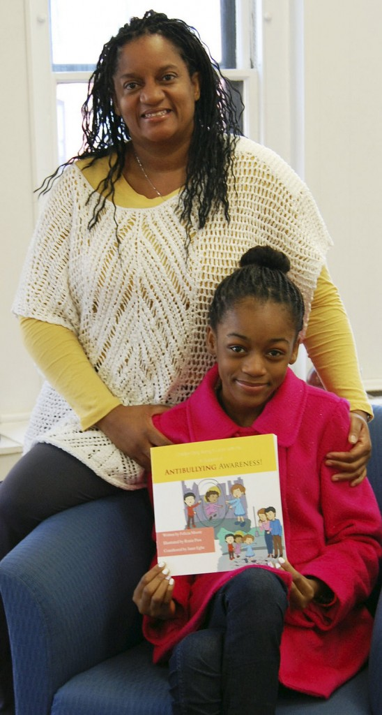 In this Jan. 21, 2013 photo, Felicia Moore, left, poses in Lynn, Mass., with her daughter, Janet Egbe, and a children's book she wrote about bullying after her daughter was bullied. (AP Photo/Daily Item of Lynn, Chris Stevens)
