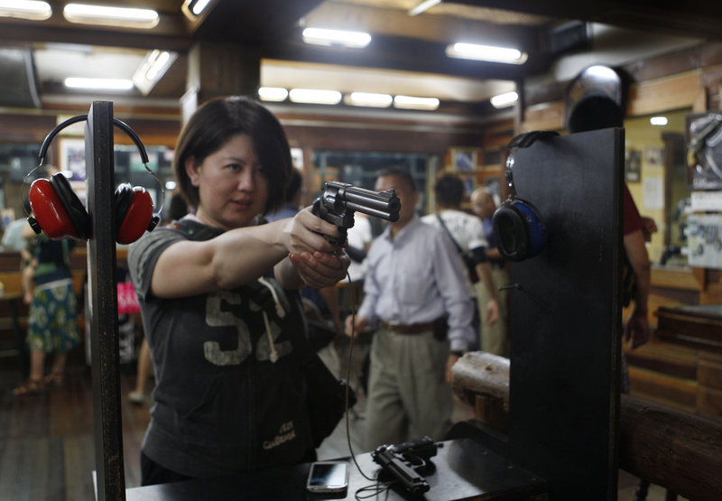 Japanese tourist Natsue Matsumoto, 38, takes aim at an indoor shooting range in Guam, where shooting is a popular tourist activity. The small U.S. territory attracts visitors who typically have little access to firearms in their own country.