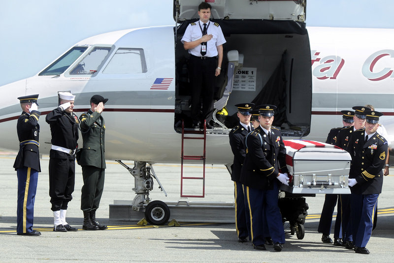 Service members salute as the remains of Staff Sgt. Eric Shaw arrive in July 2010 at Augusta State Airport, where they were escorted by the Maine Army National Guard's Honor Guard.